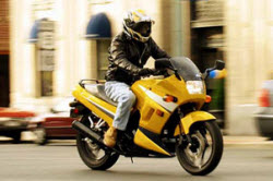 A man in a yellow helmet on a yellow motorcycle rides through a city