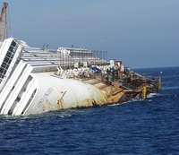 The cruise ship Costa Concordia lays on its side partially submerged