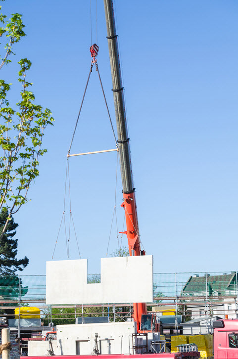 Daytime image of a large, extendable crane unloading material from a truck