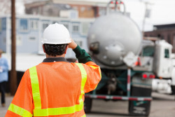 A worker guides a chemical truck onto a job site