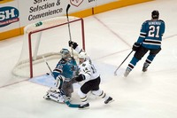 A hockey player fights the goalie for the puck near the net as a defenseman skates away