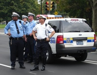 A group of police officers stand next to an SUV cruiser