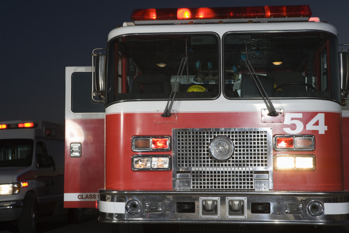 Front view of a fire engine sitting in a firehouse garage