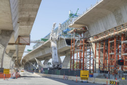 Daytime view of workers installing concrete highway overpass supports