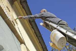 A man reaches dangerously over the top of a ladder to paint trim on a house