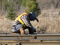 A worker sits to examine railroad tracks on a sunny day