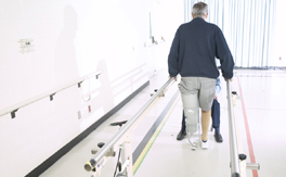 A man with a prosthetic leg undergoes physical therapy in a hospital