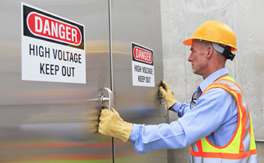 "A worker in a hard hat and gloves prepares to open a door with a ""High Voltage Keep Out"" warning sticker"