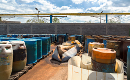Daytime view of a storage yard filled with chemicals in plastic and metal drums