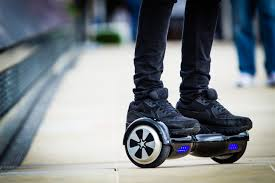 Closeup image of someone standing on a hoverboard on an urban sidewalk