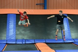 Two boys jump on trampolines at an indoor trampoline park