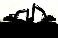 Silhouette of two bucket loaders on top of a pile of potash