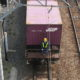 A brakeman helps to move a freight car at a railroad yard