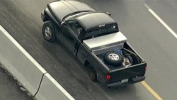 Aerial view of a black pickup truck parked on the side of a highway
