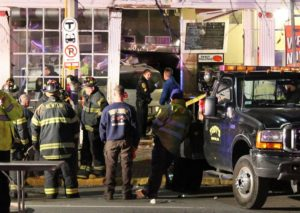 Emergency workers at the scene of a pizza shop damaged by a vehicle in Newton, Massachusetts