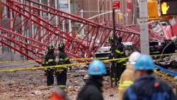 Workers look at a collapsed crane in Manhattan