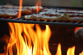 Closeup of flames cooking steaks on a grill