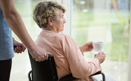 A woman in a wheelchair drinks a cup of tea at a window as an aide stands behind her