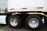 Close up daytime view of the wheels on the driver's side of a tractor trailer