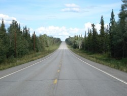 Daytime view of an open two-lane road with trees on either side